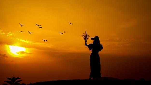 Het silhouet van een vrouw die een fotocamera houden door smartphone en grasbloem dient aard in