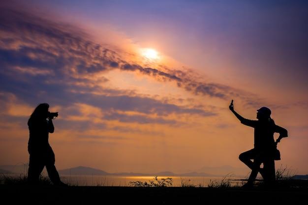 Het silhouet van een vrouw die foto's maakt tegen de zonsopgangachtergrond bij het prachtige uitzicht op de bergen van het stuwmeer.