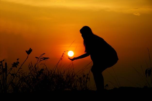 Het silhouet van een vrouw houdt de zon heeft een zonsondergang achtergrond