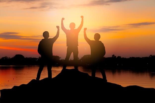 Het silhouet van gelukkig groepswerk steunt handen omhoog als succesvol, overwinning en bereikt een bedrijfsdoel in de zonsonderganghemel