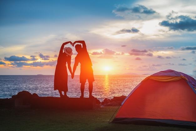 Het silhouet van het bruidspaar hand in hand in de vorm van een hart op het strand bij zonsondergang