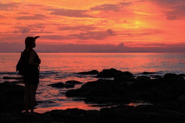 Het silhouet van jonge reizigersvrouw geniet van de zonsondergang op een strand.