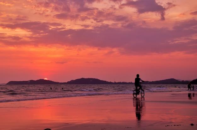 Het silhouet van jongen berijdt een fiets op het strand met zonsonderganghemel