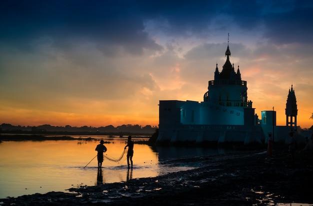 Het silhouet van lokale vissers bij het taungthaman-meer in de vroege ochtend, in de regio van mandalay