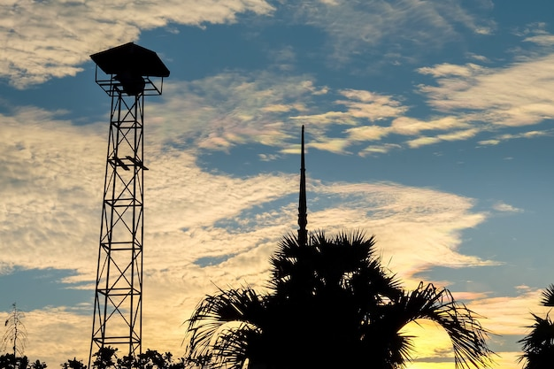 Het silhouet van luidsprekers zendt toren op de achtergrondzonsonderganghemel uit