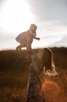 Het silhouet van mooie vrouw heft hoog haar aanbiddelijk babymeisje op in de lucht en bekijkt haar glimlachend.