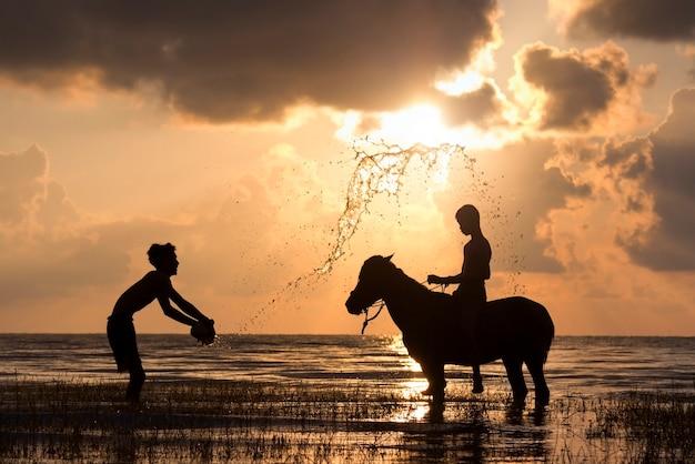 Het silhouet van twee jongens met hun paard aan de zee. zij zijn blij.
