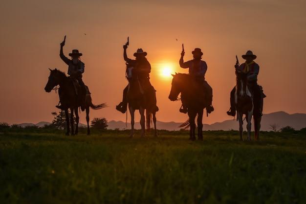 Het silhouet van vier mannen in een cowboyjurk met paarden en geweren in de hand.