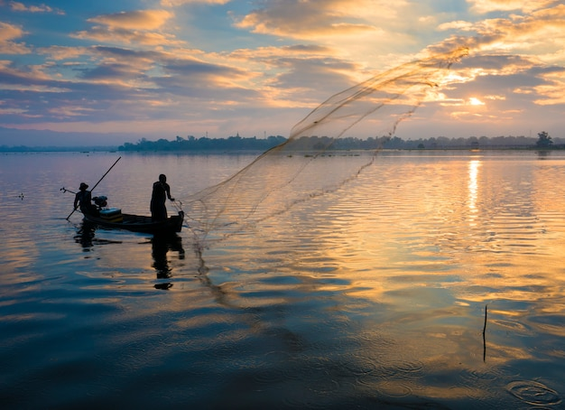 Het silhouet van visser die net in de vroege ochtend werpt