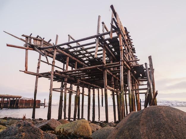 Het skelet van een vissersschuur op het strand. verlaten huis tegen de poolhemel. oud authentiek dorpje teriberka. rusland.