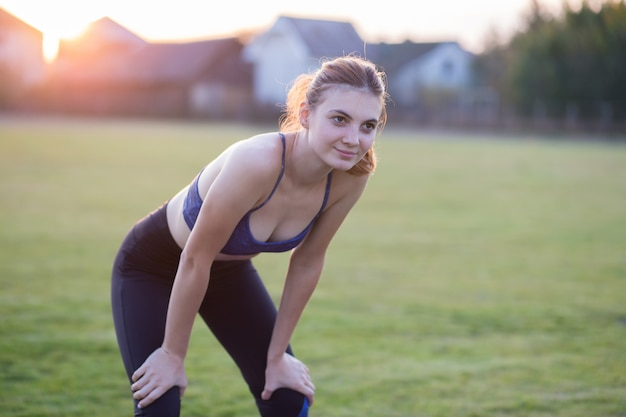 Het slanke blondemeisje speelt sporten en voert yoga uit stelt in de zomer gras behandeld stadion op een zonsondergangachtergrond. vrouw die oefeningen op de yogamat doet.