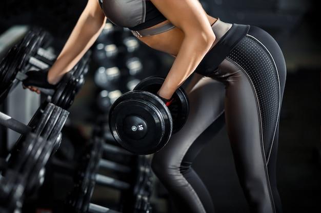 Het slanke, bodybuildermeisje, heft zware domoor op die zich voor de spiegel bevindt terwijl in de gymnastiek opleidt. sportconcept, vetverbranding en een gezonde levensstijl