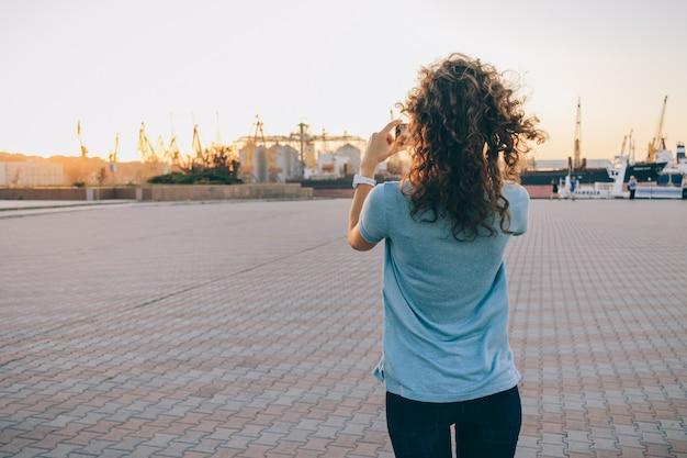 Het slanke meisje neemt beelden van stadslandschap