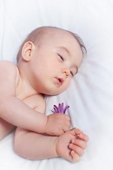 Het slapen van een baby die een bloem houdt. detailopname.