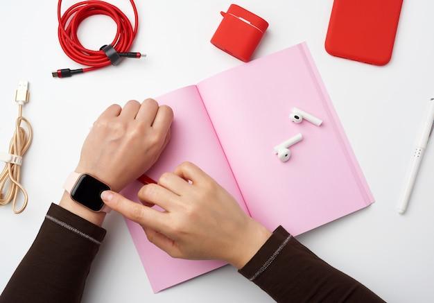 Het slimme horloge met een leeg zwart scherm bevindt zich aan zijn linkerhand, zijn rechterhand raakt het horlogescherm aan, een freelancerswerkplek met een open notebook, bovenaanzicht, thuiswerken