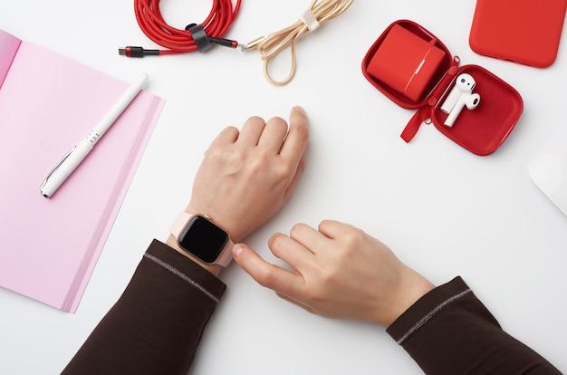 Het slimme horloge met een leeg zwart scherm bevindt zich aan zijn linkerhand, zijn rechterhand raakt het horlogescherm