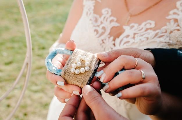 Het slot met sleutels in handen van de bruidegom en de bruid, romantisch geschenk in de vorm van een hart in de handen van een mooi stel.