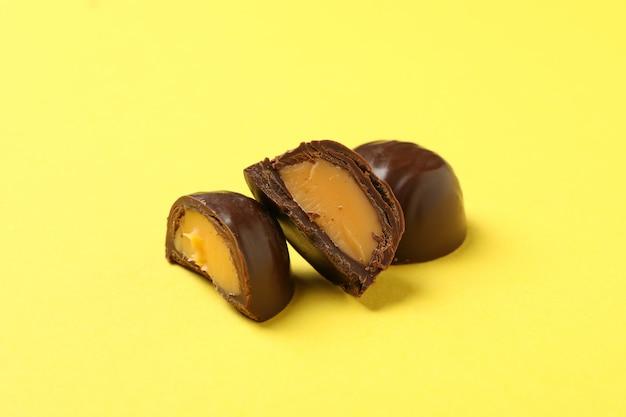 Het smakelijke chocoladesuikergoed op geel, sluit omhoog