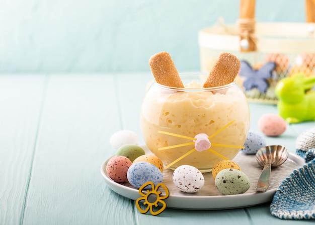 Het smakelijke dessert van de rijstebrij dat van paashaas met kleurrijke kwarteleitjes wordt verfraaid. vakantie helthy food concept met kopie ruimte
