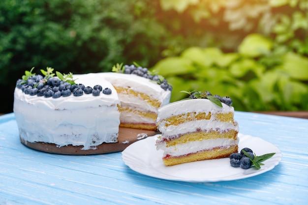 Het smakelijke het koekjeshoofdkussen van de kaastaartcake verfraaide witte roombosbessen en munttribunes op houten blauwe rustieke lijst tegen achtergrond de zomergreens.
