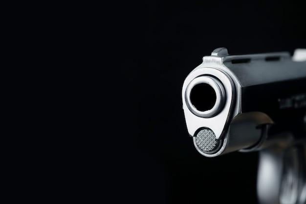 Het snuitgedeelte van de pistoolscène op een zwart achtergrondconcept abstracte wapens