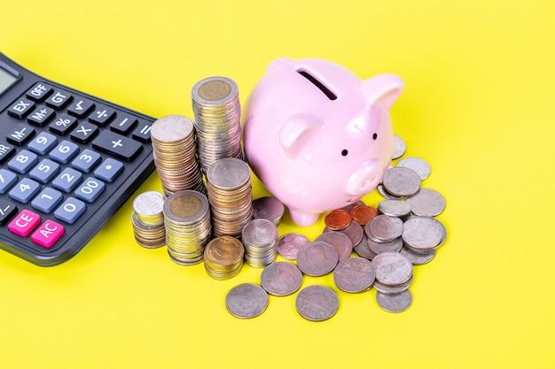 Het spaarvarken met stapel van muntstuk en calculator is op gele lijst. geld besparen, financieel concept.