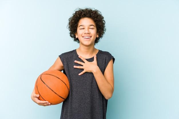 Het speelbasketbal van de jong geitjejongen dat op blauw wordt geïsoleerd lacht hardop hand houdend op borst.