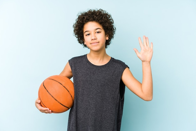 Het speelbasketbal van de jong geitjjongen dat op blauwe muur wordt geïsoleerd die vrolijk glimlachen toont nummer vijf met vingers.