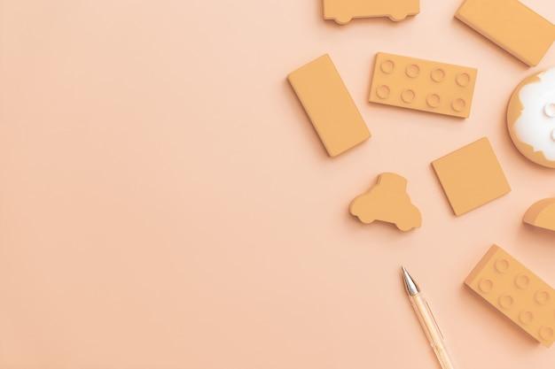 Het speelgoed van jonge geitjes op oranje achtergrond met speelgoedvlakte legt hoogste mening met leeg centrum