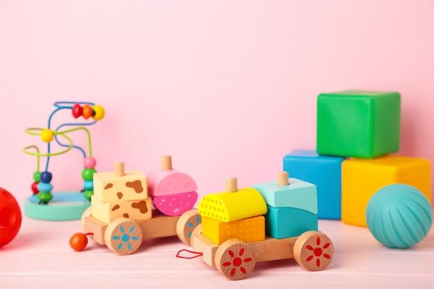 Het speelgoedinzameling van kinderen op een roze