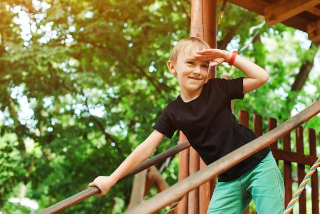 Het spelen van de jongen in een boomhut en het onderzoeken van de afstand.