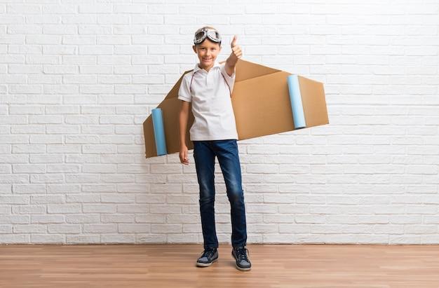 Het spelen van de jongen met de vleugels van het kartonnen vliegtuig op zijn rug die duimen op gebaar en het glimlachen geeft