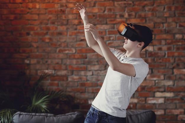 Het spelen van de jongen met vr-hoofdtelefoon thuis