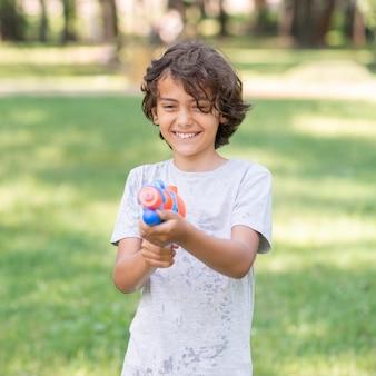 Het spelen van de jongen met waterkanon