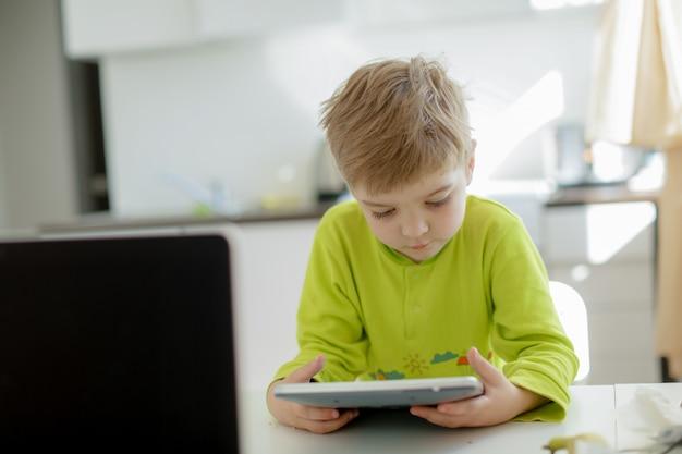 Het spelen van de jongen op elektronische gadgettablet in zijn slaapkamer. sociaal probleem van communicatie van kinderen in de moderne wereld.