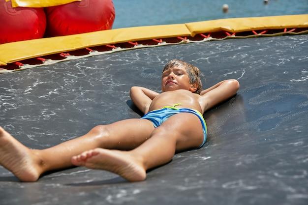 Het spelen van de jongen op watertrampoline op het overzees bij zonnige dag