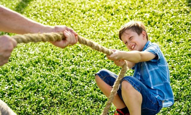 Het spelen van de jongen touwtrekwedstrijd in het park