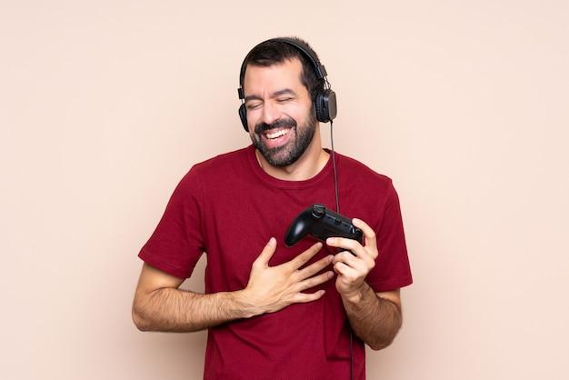Het spelen van de mens met een videospelletjecontrolemechanisme dat veel glimlacht