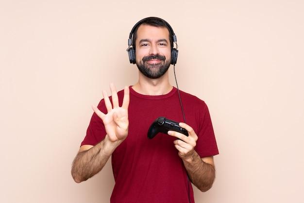Het spelen van de mens met een videospelletjecontrolemechanisme over geïsoleerde gelukkige muur en het tellen van vier met vingers