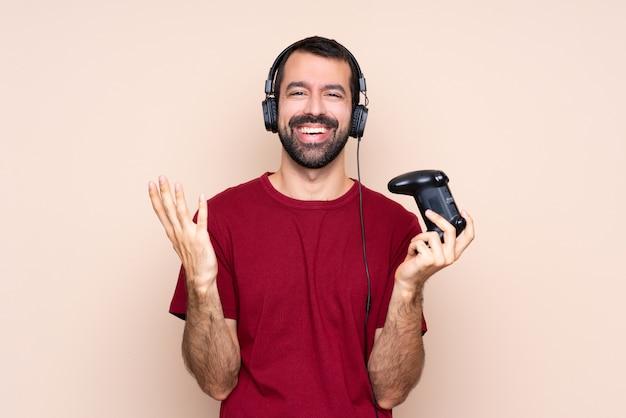 Het spelen van de mens met een videospelletjecontrolemechanisme over geïsoleerde muur die veel glimlacht