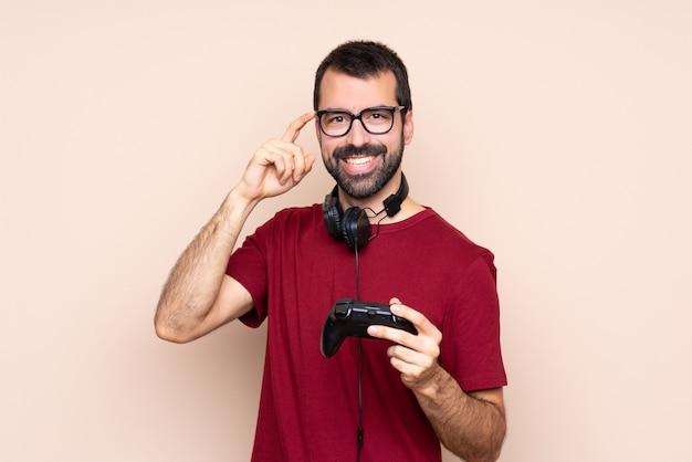 Het spelen van de mens met een videospelletjecontrolemechanisme over geïsoleerde muur met glazen en het glimlachen