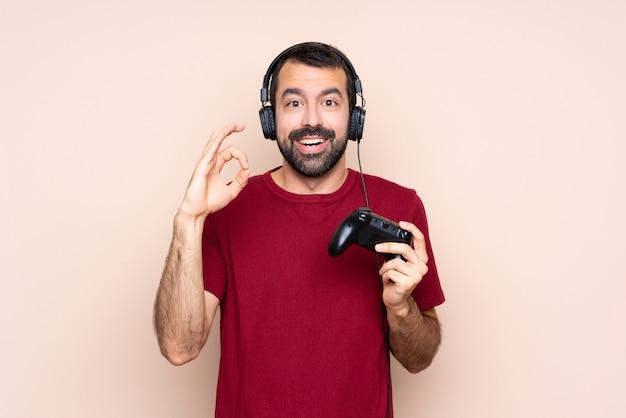 Het spelen van de mens met een videospelletjecontrolemechanisme over geïsoleerde muur verrast en tonend ok teken