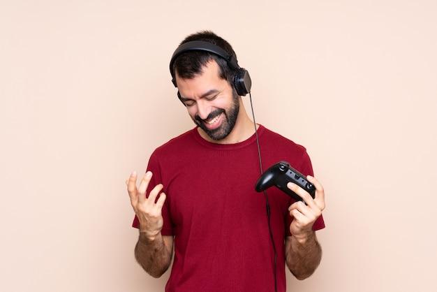 Het spelen van de mens met een videospelletjecontrolemechanisme over het geïsoleerde muur glimlachen