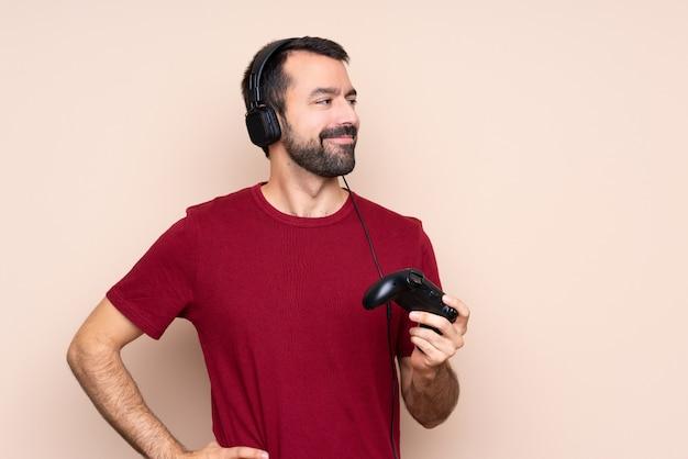 Het spelen van de mens met een videospelletjecontrolemechanisme over het geïsoleerde muur stellen met wapens bij heup en het glimlachen