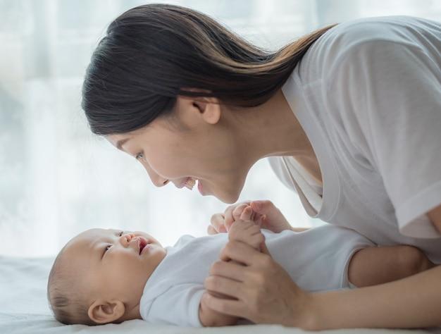 Het spelen van de moeder en van de baby in zonnige ruimte. ouder en klein kind ontspannen thuis. familie plezier samen.