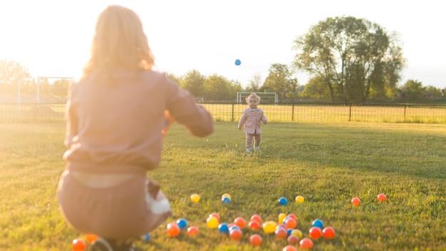 Het spelen van de moeder en van het kind met plastic ballen snakken schot