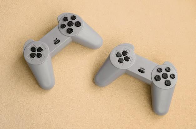Het spelen van games concept. twee pad joysticks liggen op de deken van harige oranje fleece stof.