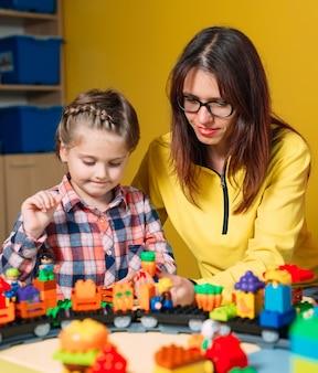 Het spelen van het kind met aannemersblokken in klasse dichtbij haar leraar