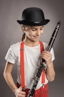 Het spelen van het meisje klarinet op grijs