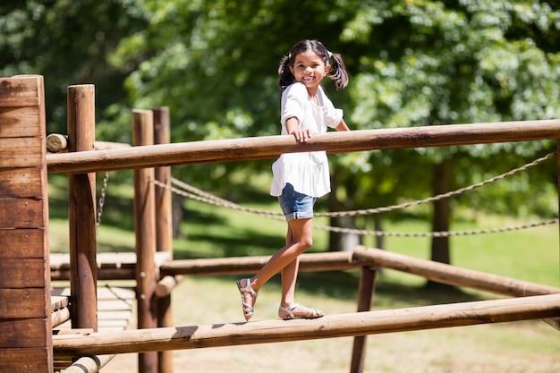 Het spelen van het meisje op een speelplaatsrit in park